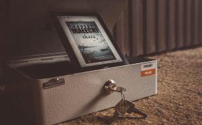 kasetka na pieniądze, stoi na betonowej podłodze, w środku nie jstoi czytnik z okładką książki Skaza Roberta Małeckiego