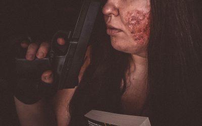 kobieta z blizną po paprzeniu na policzku trzyma pistolet i książkę Bednarka